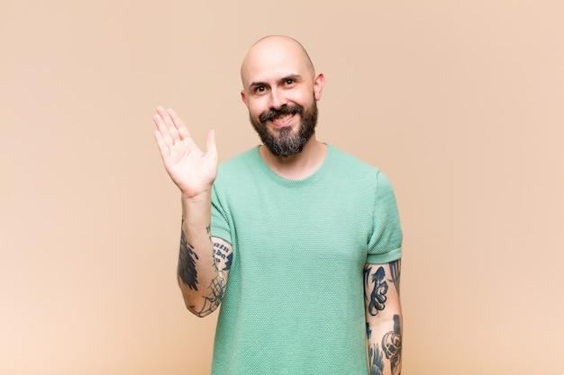はげてひげを生やした若い男が幸せにそして元気に笑って、手を振って、あなたを歓迎して挨拶するか、さようならを言う