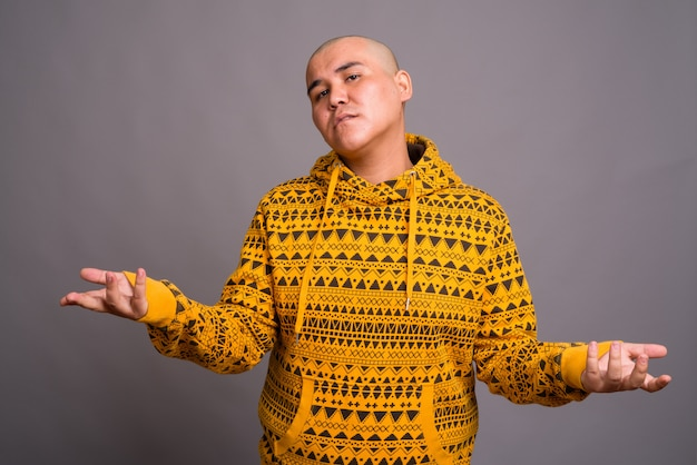 Young bald asian man wearing hoodie against gray wall