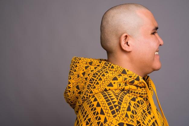 Молодой лысый азиатский мужчина носить толстовку против серой стены