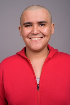 Молодой лысый мужчина в красной куртке на серой стене
