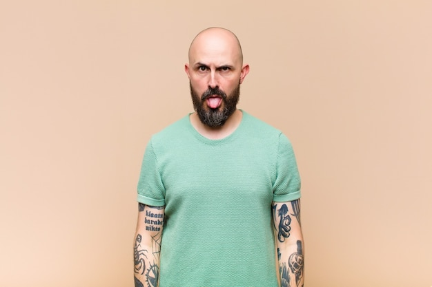 Young bald and bearded man feeling disgusted and irritated, sticking tongue out, disliking something nasty and yucky