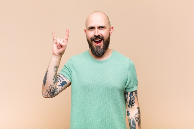 Young bald and bearded man feeling happy, fun, confident, positive and rebellious, making rock or heavy metal sign with hand