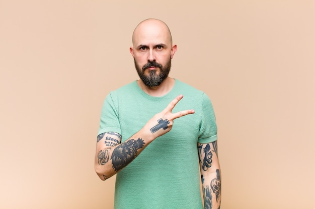 Young bald and bearded man feeling happy, positive and successful, with hand making v shape over chest, showing victory or peace