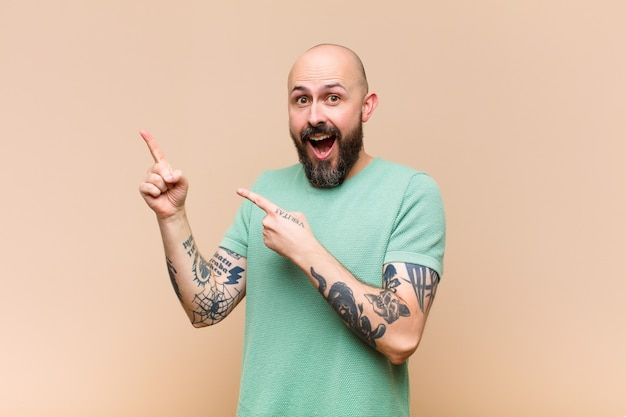 Young bald and bearded man feeling joyful and surprised, smiling with a shocked expression and pointing to the side