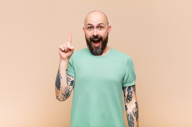Young bald and bearded man feeling like a happy and excited genius after realizing an idea, cheerfully raising finger, eureka!