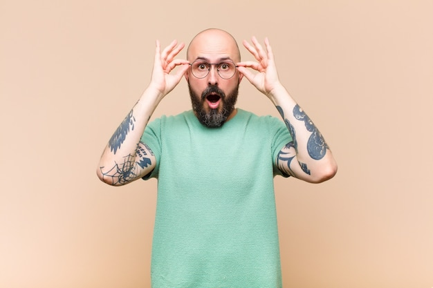 Young bald and bearded man feeling shocked, amazed and surprised, holding glasses with astonished, disbelieving look