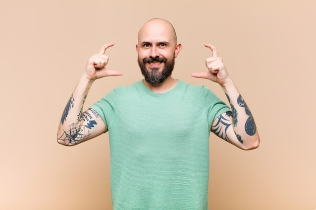 Young bald and bearded man framing or outlining own smile with both hands, looking positive and happy, wellness concept