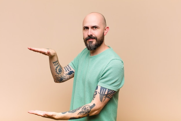 Young bald and bearded man holding an object with both hands on side copy space, showing, offering or advertising an object