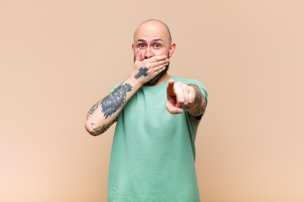 Young bald and bearded man laughing at you, pointing to camera and making fun of or mocking you