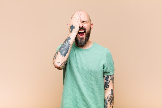 Young bald and bearded man looking sleepy, bored and yawning, with a headache and one hand covering half the face