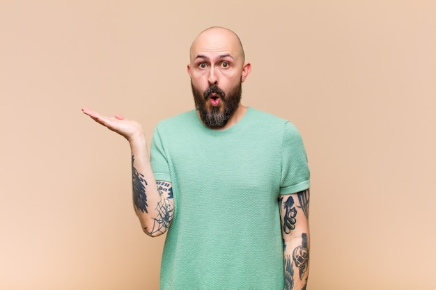 Young bald and bearded man looking surprised and shocked, with jaw dropped holding an object with an open hand on the side