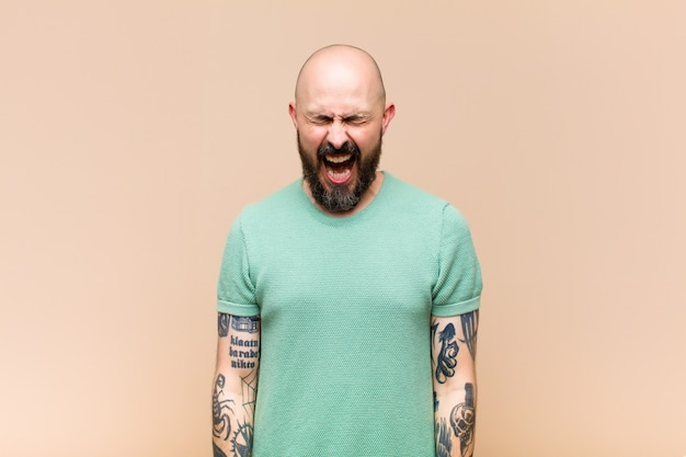 Young bald and bearded man shouting aggressively, looking very angry, frustrated, outraged or annoyed, screaming no