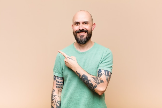 Young bald and bearded man smiling cheerfully, feeling happy and pointing to the side and upwards, showing object in copy space