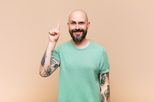 Young bald and bearded man smiling cheerfully and happily, pointing upwards with one hand to copy space