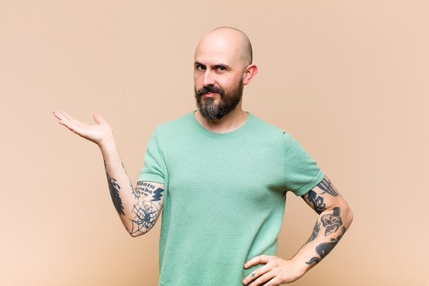 Young bald and bearded man smiling, feeling confident, successful and happy, showing concept or idea on copy space on the side