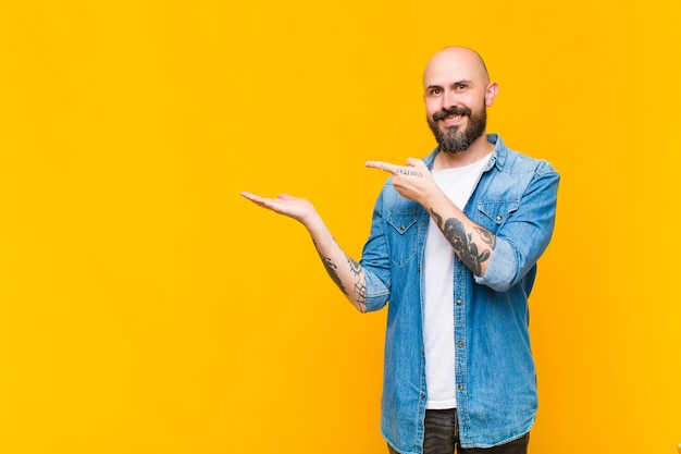 Young bald and bearded man smiling, feeling happy, carefree and satisfied, pointing to concept or idea on copy space on the side
