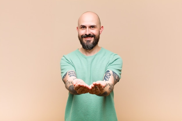 Young bald and bearded man smiling happily with friendly, confident, positive look, offering and showing an object or concept