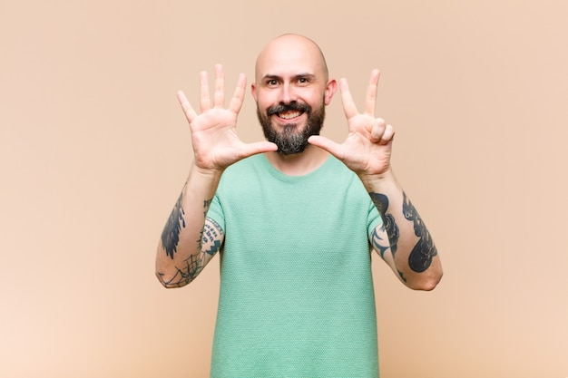 Young bald and bearded man smiling and looking friendly, showing number eight or eighth with hand forward, counting down