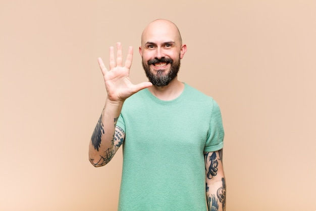 Young bald and bearded man smiling and looking friendly, showing number five or fifth with hand forward, counting down