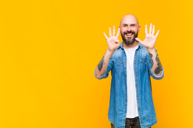 Young bald and bearded man smiling and looking friendly, showing number nine or ninth with hand forward, counting down