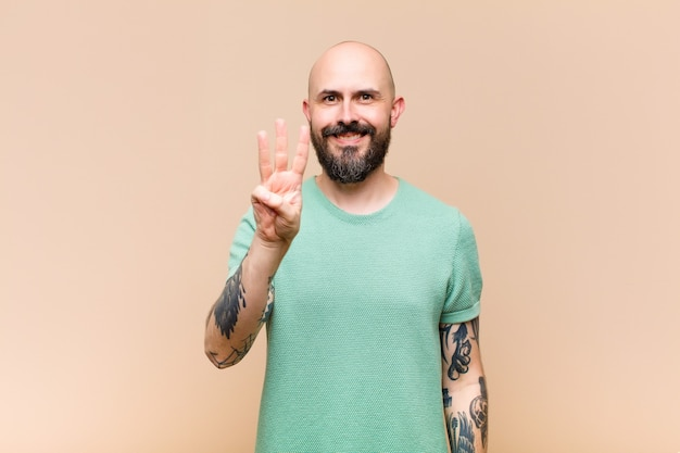 Young bald and bearded man smiling and looking friendly, showing number two or second with hand forward, counting down