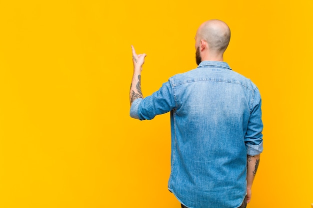 Young bald and bearded man standing and pointing to object on copy space, rear view