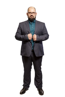 Young bald bearded man with glasses and a full-length suit. isolated over white background