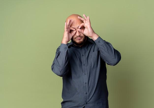 コピースペースでオリーブグリーンの背景に分離された双眼鏡として手を使用してカメラで見てジェスチャーをしている若いハゲのコールセンターの男