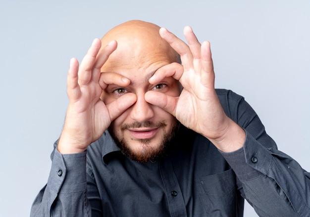 白い背景で隔離の双眼鏡として手を使用してカメラで見てジェスチャーをしている若いハゲのコールセンターの男