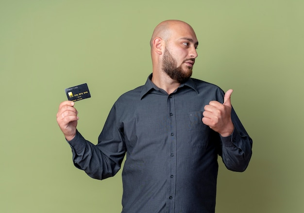 젊은 대머리 콜 센터 남자 엄지 손가락을 보여주는 신용 카드를 들고 올리브 녹색 배경에 고립 된 측면을보고