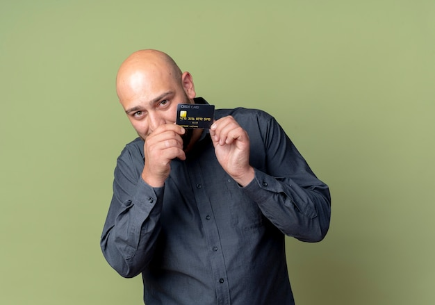 Giovane uomo calvo call center holding e guardando da dietro la carta di credito in telecamera isolata su sfondo verde oliva con spazio di copia
