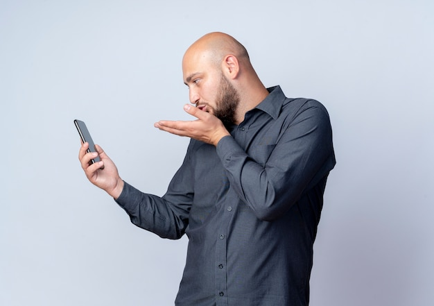 Young bald call center man holding and looking at mobile phone and sending blow kiss isolated on white background with copy space