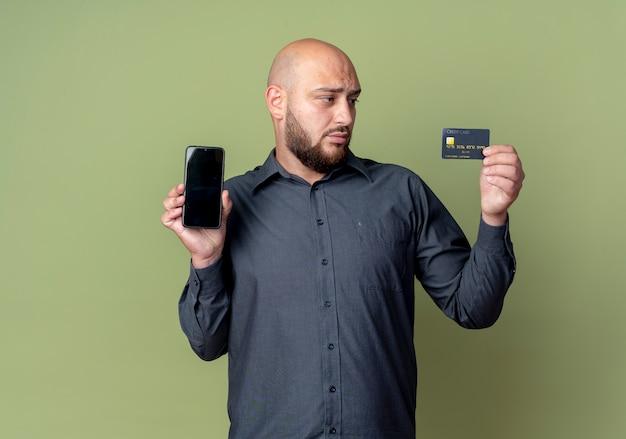 Молодой лысый человек колл-центра держит мобильный телефон и кредитную карту и смотрит на карту, изолированную на оливково-зеленом фоне с копией пространства
