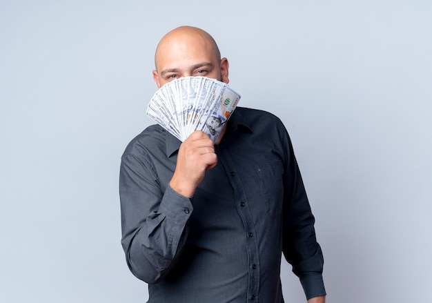 Young bald call center man looking at camera from behind money isolated on white background with copy space