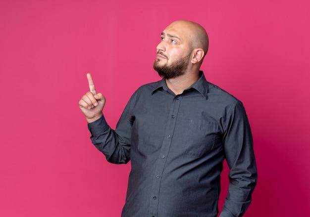 Giovane calvo call center uomo guardando a lato e alzando il dito isolato su sfondo cremisi con copia spazio