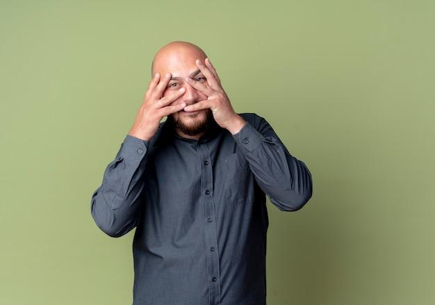 Uomo calvo giovane call center che mette le mani sul viso e che guarda l'obbiettivo attraverso le dita isolate su priorità bassa verde oliva con lo spazio della copia
