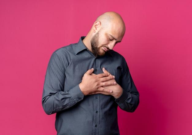 Молодой лысый человек из колл-центра кладет руки на грудь, глядя вниз на малиновом фоне с копией пространства