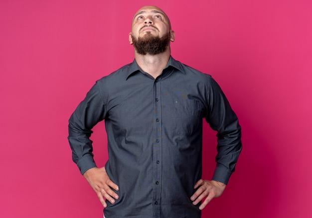 腰に手を置き、コピースペースで深紅色の背景に孤立して見上げる若いハゲのコールセンターの男