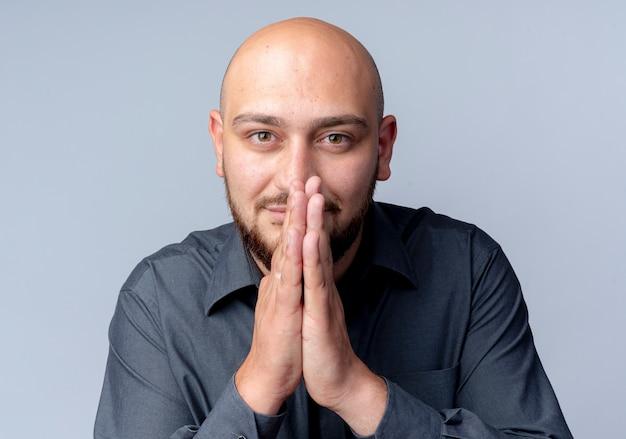 Giovane uomo calvo del call center che mette le mani insieme nel gesto di preghiera che guarda l'obbiettivo isolato su priorità bassa bianca