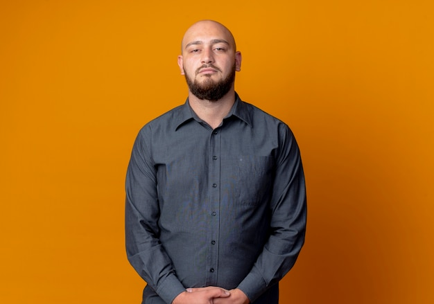 Young bald call center man standing and looking at camera and keeping hands together isolated on orange background with copy space