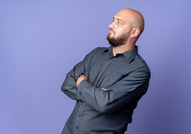 コピースペースと紫色の背景にまっすぐに孤立してまっすぐに見える閉じた姿勢で立っている若いハゲのコールセンターの男
