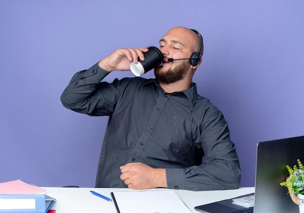 보라색 배경에 고립 된 닫힌 눈으로 커피를 마시는 작업 도구와 책상에 앉아 헤드셋을 착용하는 젊은 대머리 콜 센터 남자