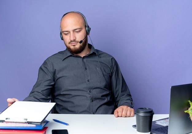 紫色の背景に分離されたクリップボードに触れて見て作業ツールと机に座っているヘッドセットを身に着けている若いハゲコールセンターの男