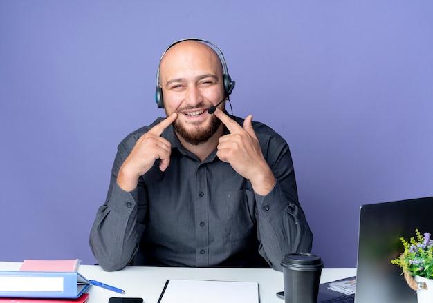 Giovane calvo call center uomo che indossa l'auricolare seduto alla scrivania con strumenti di lavoro mettendo le dita sui lati della bocca fingendo sorriso e guardando la telecamera isolata su sfondo viola