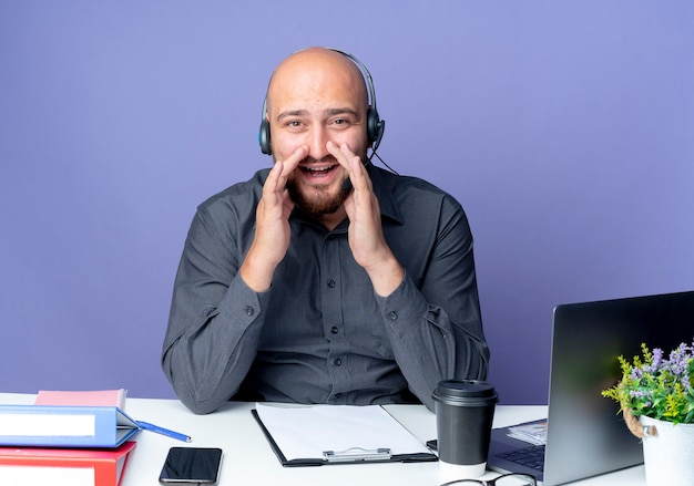 Young bald call center man wearing headset sitting at desk with work tools putting hands around mouth calling out someone and looking at camera isolated on purple background