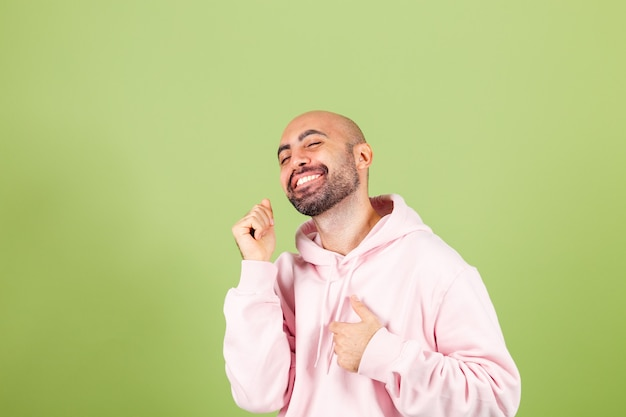 ピンクのパーカーで孤立した、幸せで陽気な、笑顔の動くカジュアルで自信を持って音楽を聴いている若いハゲ白人男性