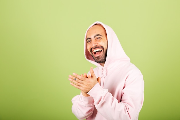 ピンクのパーカーで孤立した、幸せな拍手と拍手、幸せで楽しい、誇らしげな手を一緒に笑って若いハゲ白人男性