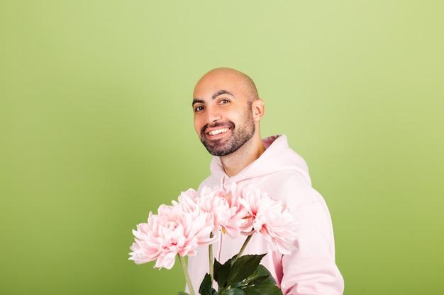 孤立したピンクのパーカーの若いハゲ白人男性、幸せな笑顔の花の花束を保持します。