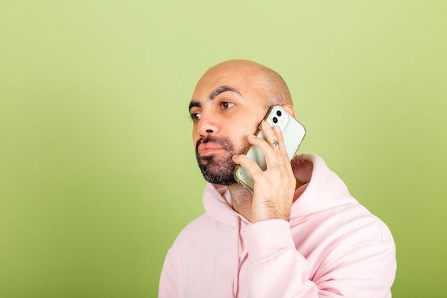 고립 된 분홍색 까마귀에 젊은 대머리 백인 남자, 전화 보류 지루 슬픈 불행한 얼굴로 오디오 메시지 대화를 들어