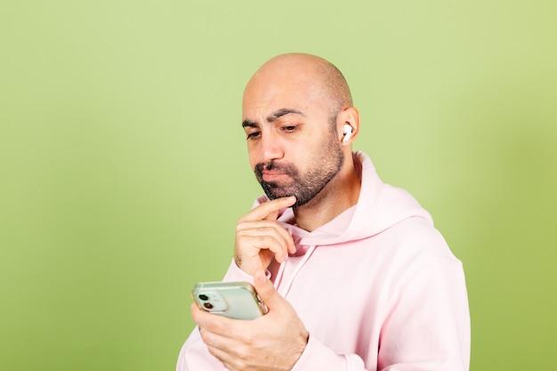 Молодой лысый кавказский мужчина в розовой толстовке с капюшоном изолирован, задумчиво держит телефон за подбородок